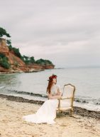 bridal style shoot with floral crown in a secret cove setting seated on a vintage style chair