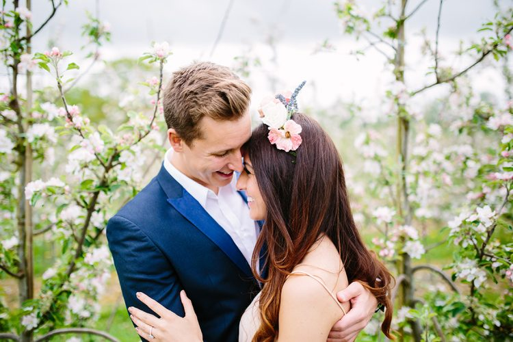 elegant couple embrace in an orchard of blossoms