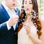 couple blowing dandelions at their engagement session