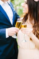 couple say cheers with champagne glasses at their engagement session