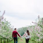 engagement session couple walk holding hands through the orchard