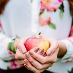 bride to be holding an apple displaying her beautiful engagement ring