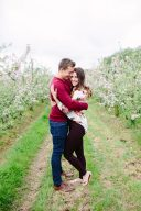 engagement session couple in a pretty blossom tree orchard