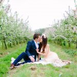 couple sat upon pretty blanket in the middle of an orchard