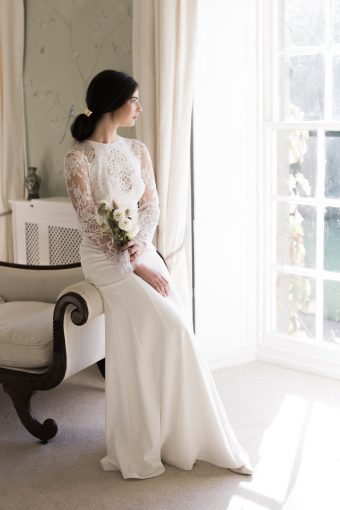 brides is seated in the room where she is getting ready at pennard house