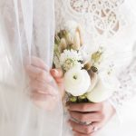 bride holds small bouquet of flowers by jay archer