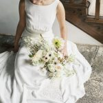 bride sat with her bouquet of flowers by jay archer