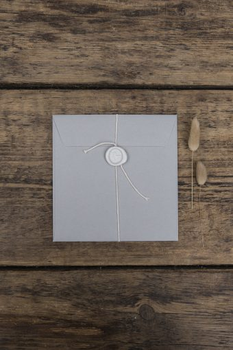 grey wedding stationery envelope with a classic wax seal and bound with yarn