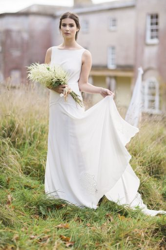 bridal portriat outside in the gardens of pennard house wearing a gown from luellas bridal holding a bouquet of natural flowers for a countryside feel
