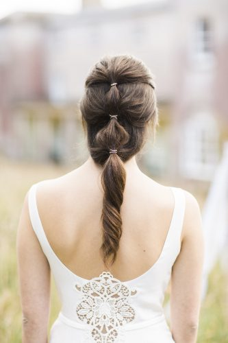 statement on trend bridal hair style with loose gathering of the hair and tied at the back