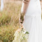 the bride holding a bouquet of natural flowers to add to the natural and outdoors feel of this wedding style