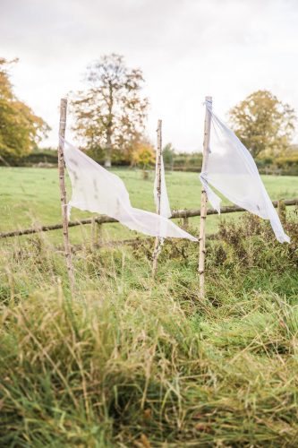 white silk flags blow delicately in the wind as a feature for this garden wedding