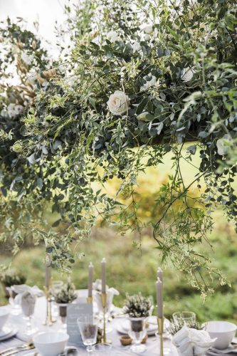 a canopy of roses and green foliage hangs over the table of this wedding setting to make a statement and add to the meadow setting