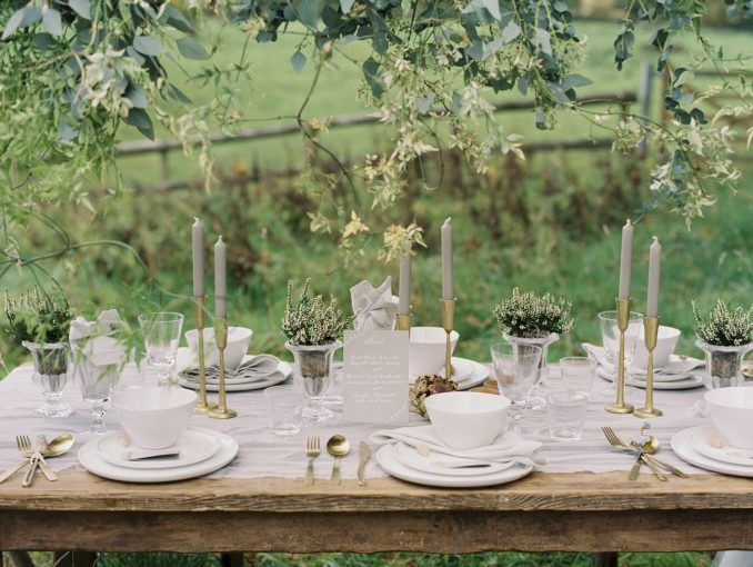 a rustic wooden table set in a meadow with a canopy of roses and foliage above set for a countryside wedding