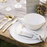 beautiful white and grey table setting for an outdoor garden wedding with gold cutlery and natural floral accents