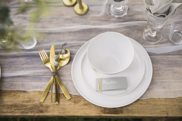 a vintage wooden table with gold cutlery and white tableware styled for a wedding in the outdoors