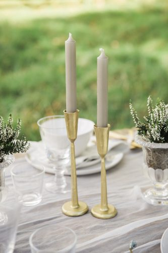 gold candlesticks holding grey tall tapers for the table setting of this outdoor wedding