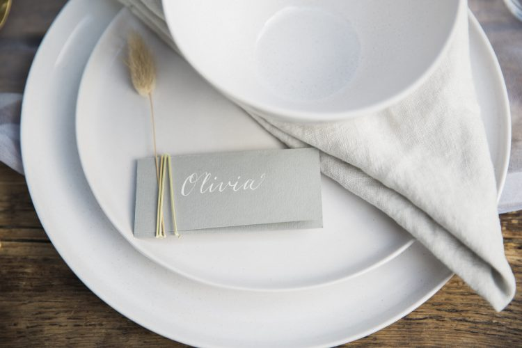 calligraphy name cards with natural foliage and white tableware