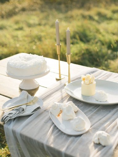 beautifully design dessert table with silk runner and tall taper candles and desserts