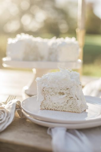 creamy white cake cut open to show the delicious layers of buttercream inside