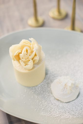 scrumptious white cake with white chocolate flower on top by natural cake company