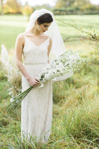 English countryside setting for a bridal portrait holding tall florals