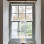 window at pennard house with tall hurrican lantern and cadle