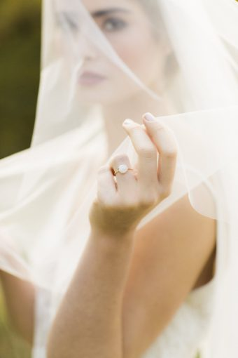 Brides hand holding her viel and showing her engagement ring