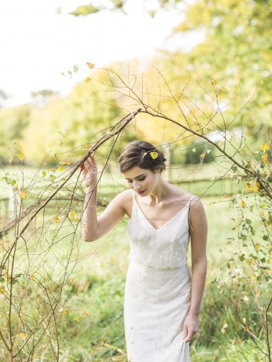 Bride wanders through the countryside wearing dress by Luellas Bridal