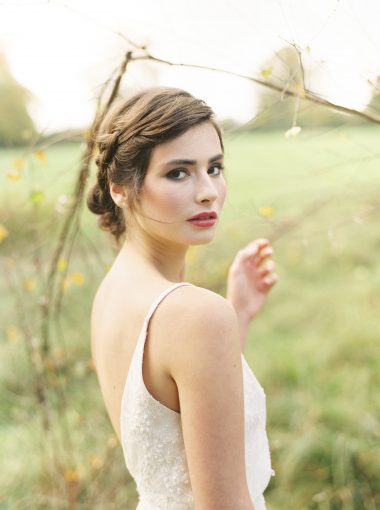 bridal portrait in the grounds of Pennard house wearing a loose braid and bun hairstyle and red lipstick