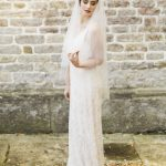 bride poses by a brick wall of pennard house wearing a gown from luellas bridal