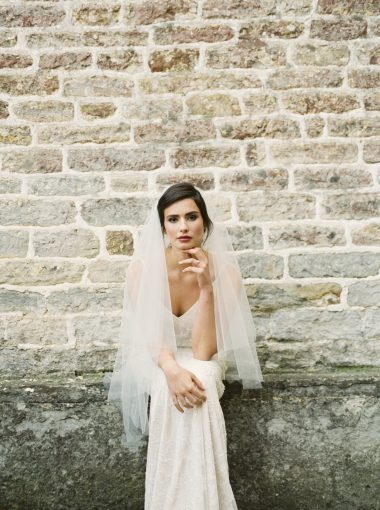 bride is seated by a brick wall of pennard house wearing a gown from luellas bridal