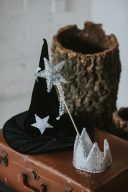 wizard hat and magic wand and sequin crown displayed on a vintage suitcase