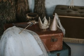 fable heart pieces like tutu wand and crown displayed on a vintage suitcase