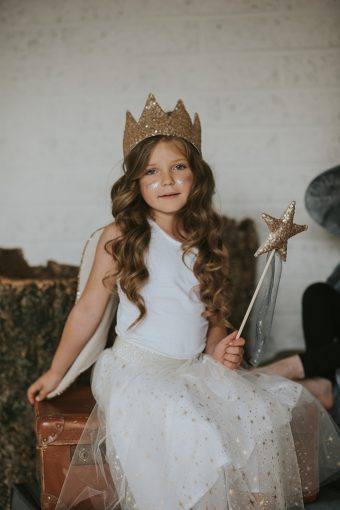 little girl wearing star print tutu with gold star wand and sequin crown