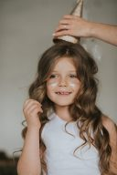 little girl with gold dust on her cheeks and wearing the gold wimple hat from fable heart