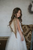 little girl wearing the gold wings to dress up as a fairy or angel from fable heart