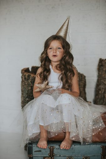 little girl wearing star tutu with want and crown