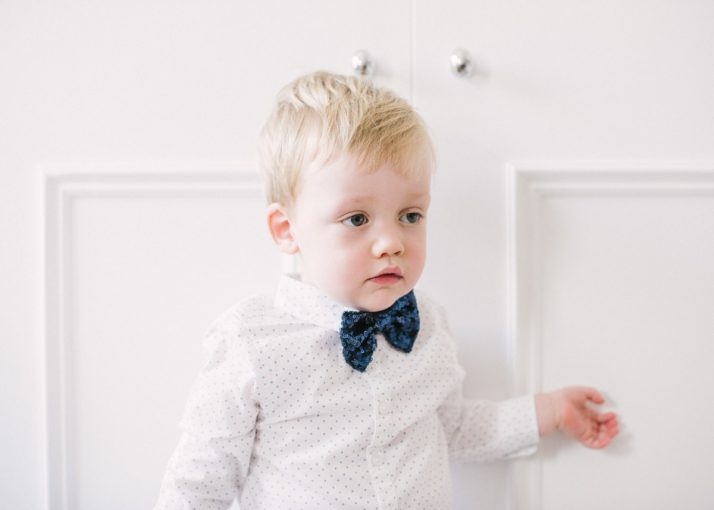 little boy wearing a white shirt and navy sequin bow tie
