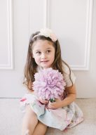 little girl wearing a floral party dress and playing with a lilac pompom