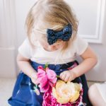 little girl wearing a navy sequin bow accessory in her hair