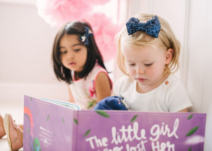 little girls enjoying reading the lost my name picture book together