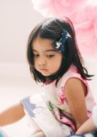 little girl wearing a navy bow accessory in her hair
