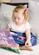 little girl reading the lost my name picture book