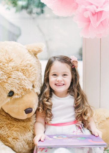 little girl sat with a huge teddy bear