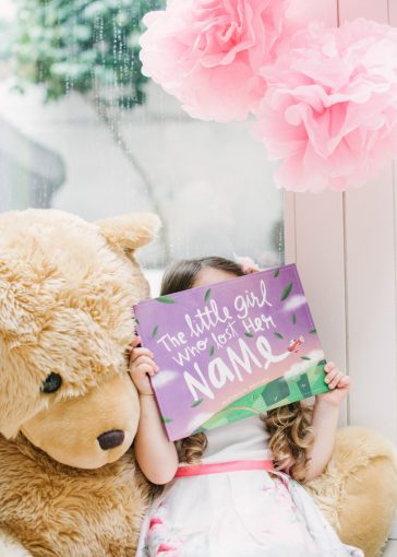 little girl sat with a huge teddy bear whilst holding up the lost my name picture book