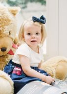 little girl sat with a huge teddy bear and reading the lost my name picture book