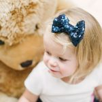 little girl sat with a large teddy and wearing a navy sequin bow in her hair