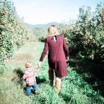 Mother and young son hold hands whilst walking through the apple trees