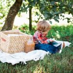 Little boy sits reading a book on a picnic blanket